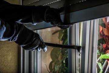 mit einem Brecheisen versucht ein Einbrecher nachts in ein Haus einzudringen