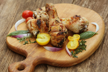 Grilled chicken legs with rosemary served on cutting board Dinner background