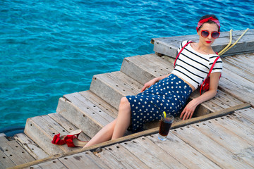 A girl on a wooden dock waiting for a boat
