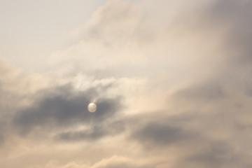 Full moon peeks through break in the clouds .