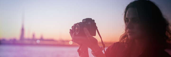 Beautiful young woman shoots on the camera views of the night city, St. Petersburg Russia, panorama, banner,