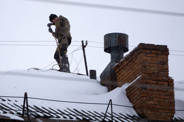 Chimney sweep man in work uniform cleaning chimney on building roof .
