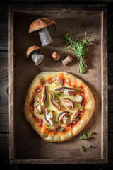 Homemade rustic pizza in old wooden box