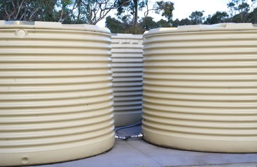 Set of three outdoor rainwater tanks on a farm in Australia with white corrugated sheeting sides
