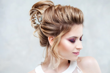Wedding style. Beautiful young bride with luxury wedding hairstyle