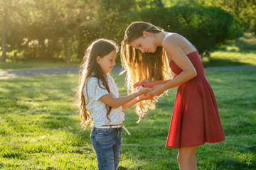 caring and beautiful long-haired mother in cocktail red dress wipes her daughter's hands with wet napkins in the park in summer . antibacterial napkins and freshness concept