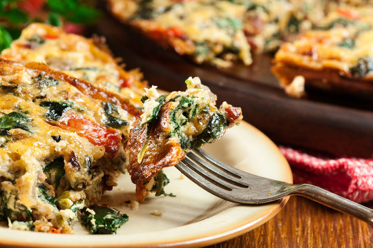 Portion of frittata made of eggs, mushrooms and spinach