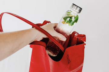 Transparent bottle with water infused with lemon and peppermint leaves to take with on hot summer days. Body parts, hand putting the bottle into red tote bag. White background, isolated, copy space.
