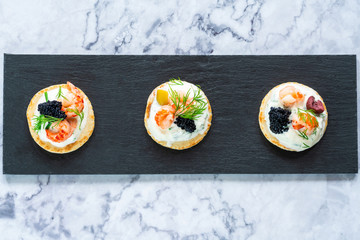 Cocktail blinis with crayfish, caviar and sour cream - gourmet party food - top view