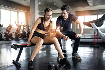 Beautiful young woman exercising on exercise machine with help by personal trainer in gym.