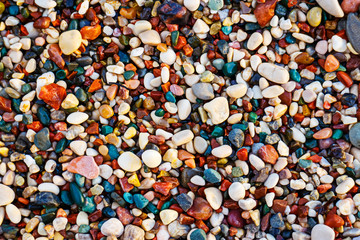 Multicolored sea pebbles on the beach, abstract background