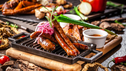 Arabian cuisine in Dubai. Assorted fried sausages on a grill, with sauce, on a wooden board. The concept is a beautiful serve in the restaurant. Background image.