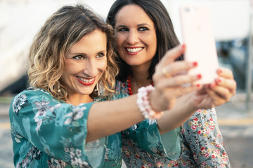two adult woman smiling and making selfies with a smartphone in open air