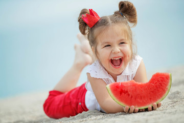 Child with a watermelon at sea