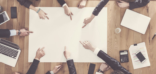 Business people sitting at table and pointing finger to blank paper