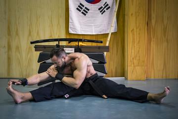 Artes marciales. Hombre fuerte con grandes músculos estirando. Defensa personal.