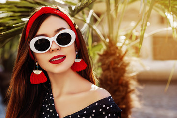Outdoor close up portrait of young beautiful fashionable woman wearing stylish red headband, white oval sunglasses, tassel earrings, polka dot blouse, posing in street. Summer fashion. Copy space