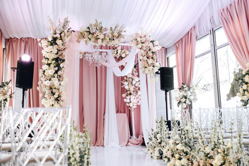 The wedding zone is decorated with white and peach cloth, crystal chandelier, transparent chairs for guests and beautiful floral arrangements of roses