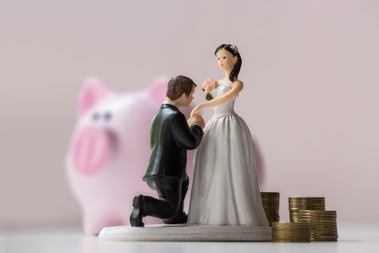 statuette of groom and bride with coins on pink background. Moneybox and wedding economy