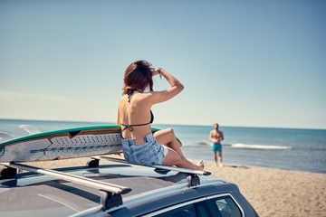 beautiful surfer girl sitting on the car and getting ready for surfing Vacation. Extreme Sport.