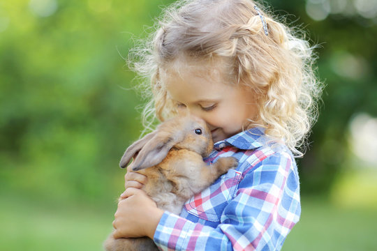 Girl with a cute little rabbit, outdoor, summer day