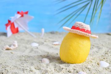 Creative minimal summer idea. Lemon citrus hipster in bamboo hat and beach umbrella on sand. Tropical beach concept. Creative art. Copy space