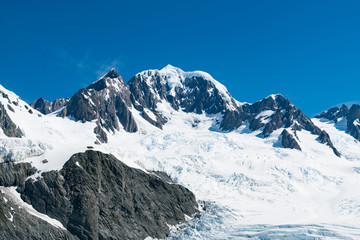 Fox glacier with volcano black rock mountain with blue sky background, New Zealand natural landscape