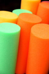 colorful pool noodles background, pool or therapy or swim noodles in modern colors detail shot