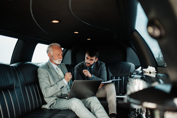 Senior businessman and his assistant sitting in limousine and celebrating their job success.