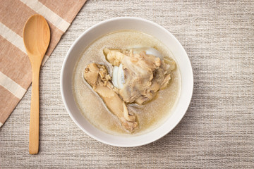 Bowl of pork bone soup with herbs on gray table mat with wooden spoon