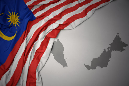 waving colorful national flag and map of malaysia.