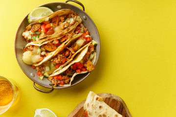 Overhead image of mexican tacos with chili con carnes and grated cheese served over a yellow background with copy space