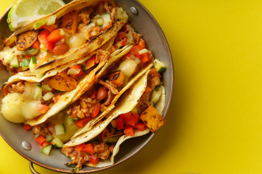 Close up of mexican tacos with chili con carnes and grated cheese served over a yellow background with text space