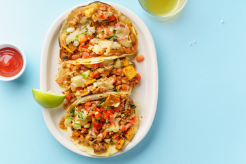 Overhead image of mexican tacos with chili con carne, sweet potatoes and grated cheese served over a blue background. Text space