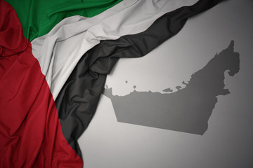waving colorful national flag and map of united arab emirates.