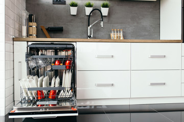 Modern open dishwasher with clean dishes in the white kitchen.