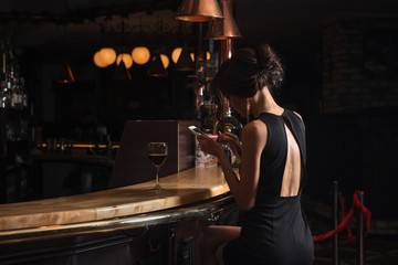 Beautiful elegant lady with a smartphone and a glass of wine in a restaurant