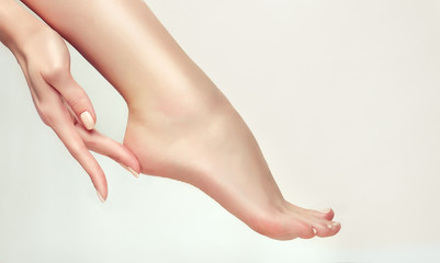 Perfect clean female feet . Beautiful and elegant groomed girl's hand touching  her foot  heel . Spa ,scrub and foot care .