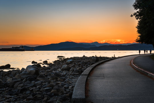 Beautiful Orange Sunset over the Seawall of Stanley Park and English Bay. Vancouver, BC, Canada.
