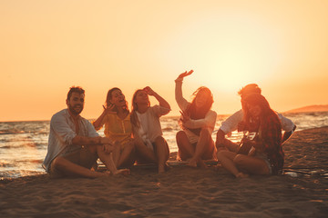 Happy friends sitting on the beach singing and playing guitar during the sunset
