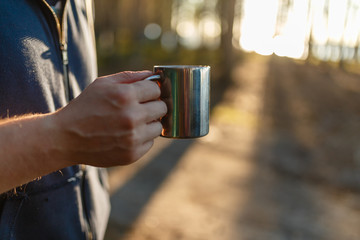 Close - up of iron camping mug with a warm drink in the hands of a male traveler on a forest and sunset background. Concept of camping in the forest. Picnic on a warm summer evening at sunset.