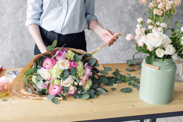 Woman florist creating beautiful bouquet in flower shop. Working in flower shop. Girl assistant or owner in floral design studio, making decorations and arrangements.