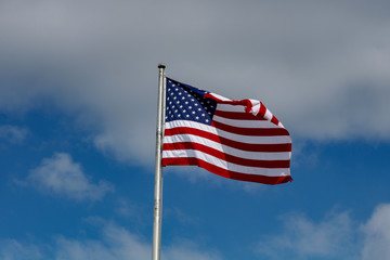 American Flag Against a Blue and Cloudy Sky