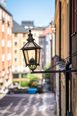City view of a old vintage street light mounted on a exterior wall in Stockholm Sweden.