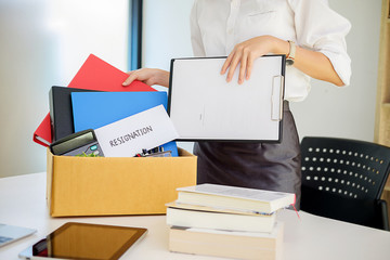 Business woman packing her belongings in cardboard box on desk leaving his office with his personal effects.