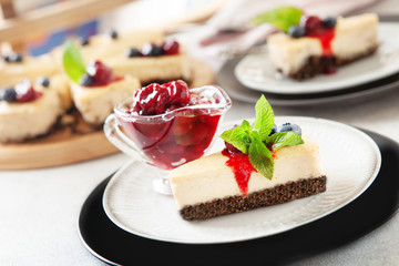 Classic New York cheesecake with fresh berries and cherry sauce on white plate