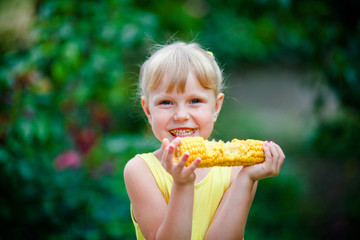 The cheerful girl eats corn on a farm.