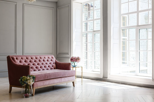 White room with pink sofa-bed, flowers in glass jug and mirror near the window. Classic interior design