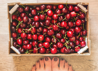 Ripe cherries in wooden box on wooden surface