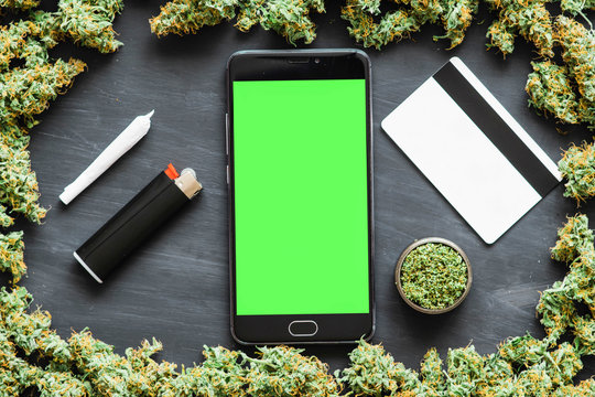 Bank credit card, online shopping concept Black smartphone with green screen for chromakey and key ring. Weed, Grinder, lighter, joint A lot of marijuana, fresh buds of cannabis many weed.